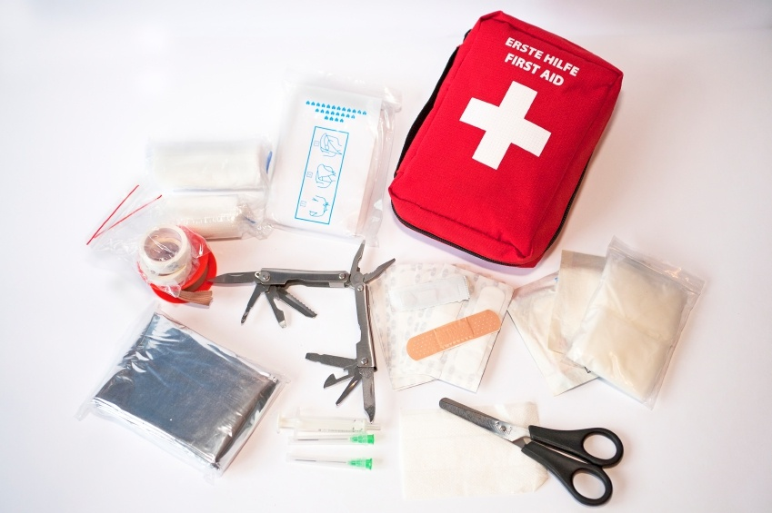 """Open first aid kit with bandages, scissors, """"triangle scarf"""", syringe, plaster, knife, tools, gauze, etc"""