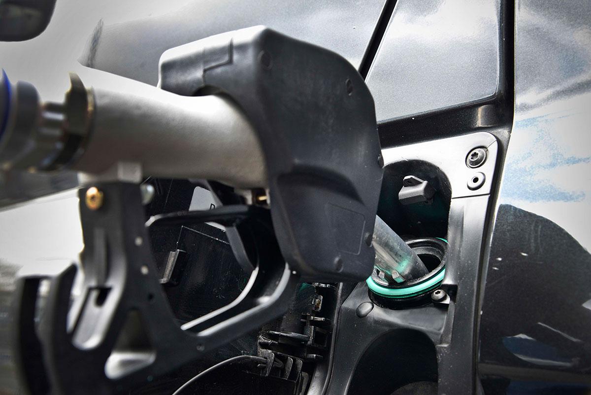 a black fuel pump filling a black vehicle