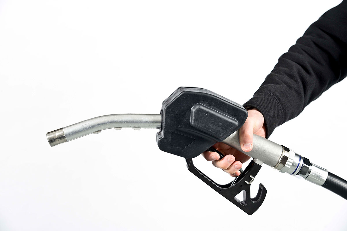 person holding a black fuel filler pump nozzle on a white background
