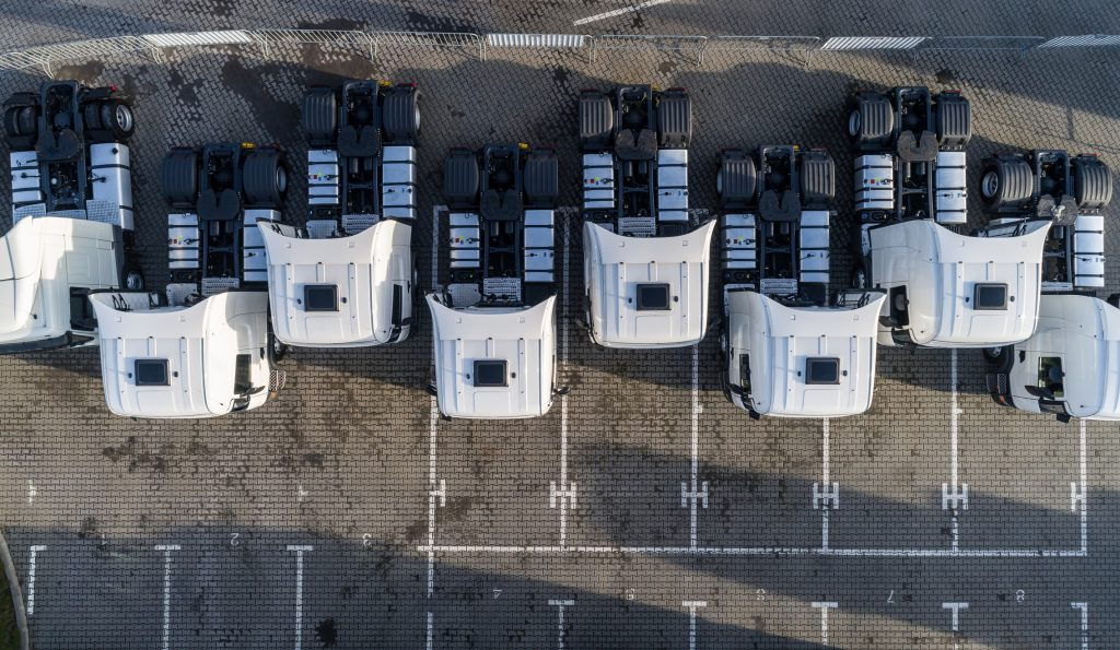 Aerial drone view of parked white trucks. Road transport